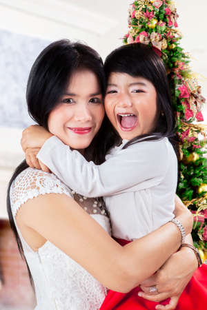 Happy mother and her daughter smiling on camera at home in christmas day photo
