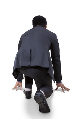 Rear view of businessman take a ready position to race and compete