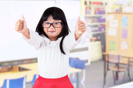 Cheerful little girl showing thumbs-up in the kindergarten classroom photo