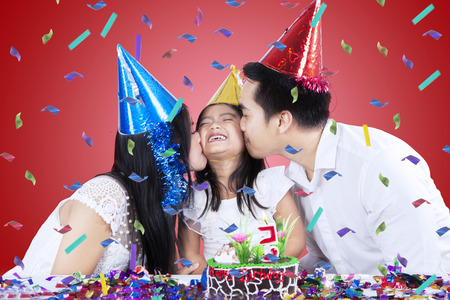 Two asian parents kiss their daughter in birthday party photo