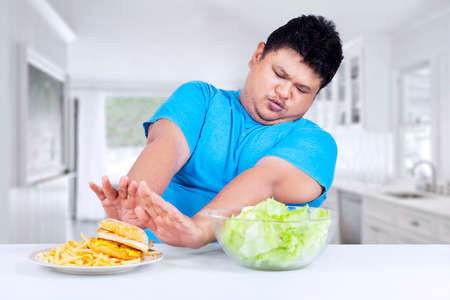 avoid: Overweight person refuse to eat fast food and choose vegetable in the kitchen Stock Photo