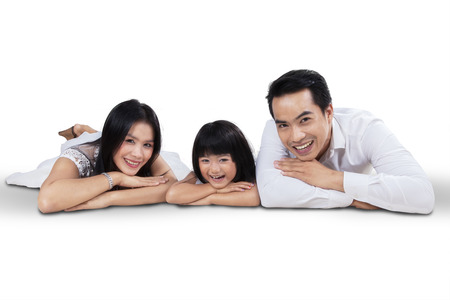 Portrait of happy family lying in studio and smiling at camera, isolated on white