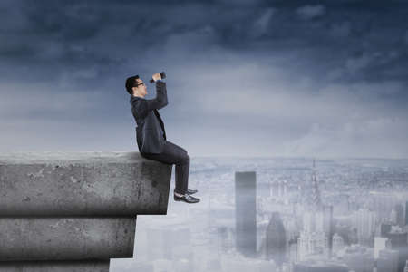 seeking solution: Young businessperson sitting on rooftop and using binocular for looking a solution