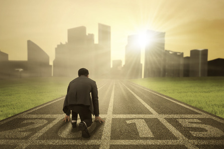 game of chance: Business person in ready position on track for running and chasing his aim