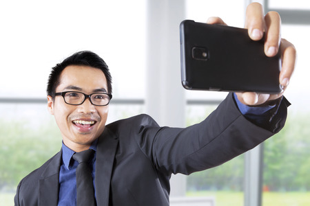 Asian businessman taking self portrait with smartphone in office photo