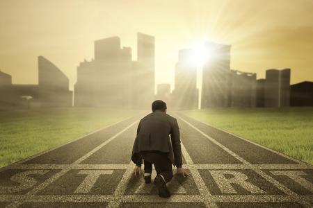 dream: Zadní pohled na podnikatele v pohotovostní poloze na startovní čáře soutěžit