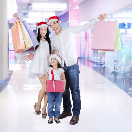 Joyful family holding shopping bags and christmas gift in the shopping center photo