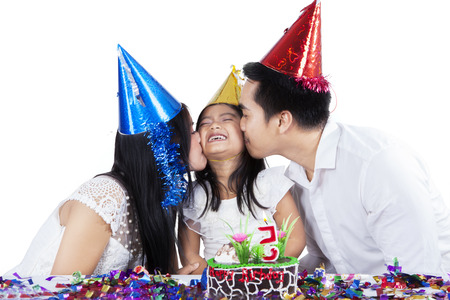 Two parents kiss their daughter in birthday party, isolated over white background photo
