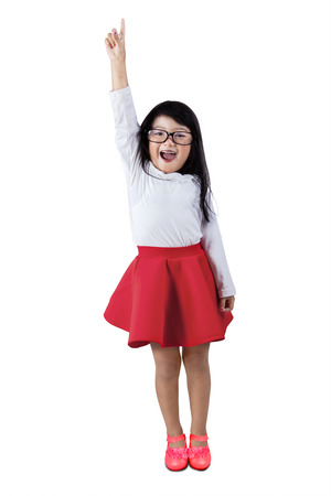 to raise: Happy little asian girl raises hand, isolated over white background