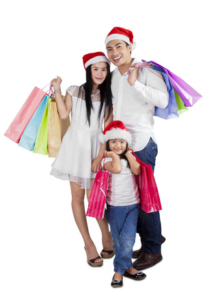 Three member of happy family holding shopping bags to celebrate christmas by shopping together photo