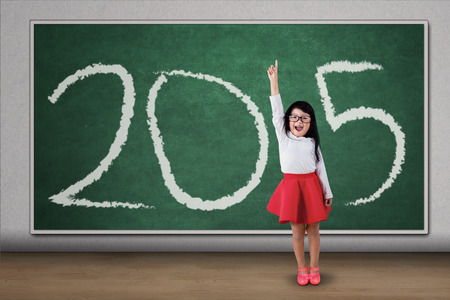 Sweet girl standing in class, raised her hand and forming number 2015 photo