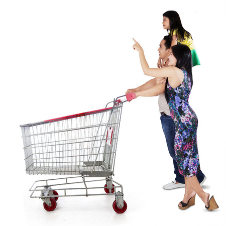 Three member of happy family pushing shopping cart and looking at copyspace