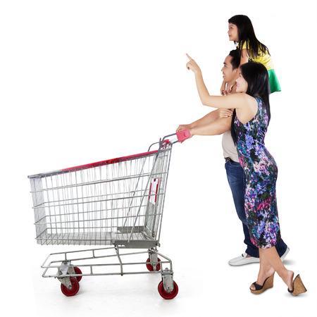 Três membros da família feliz empurrando carrinho de compras e olhando para copyspace
