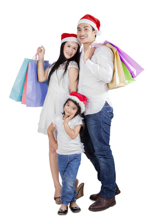 Asian family posing and smiling on camera while carrying shopping bags photo