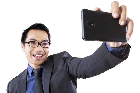 Spaanse zakenman met behulp van smartphone foto van zichzelf te nemen Stockfoto