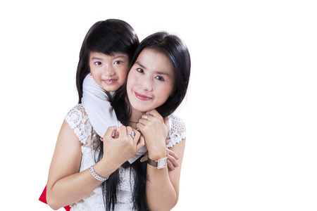 Joyful girl smiling and looking at camera while hugging her mother from the back photo