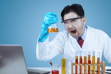 Male crazy asian scientist doing research with laptop computer and chemistry fluid photo