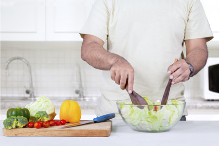 Closeup of man preparing healthy and tasty salad in kitchen photo