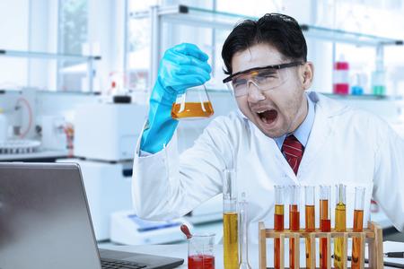 industria quimica: Persona asiática que trabaja en el laboratorio y que hace el experimento con el líquido químico