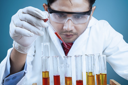 biochemist: Young scientist using chemical fluid for doing experiment in laboratory