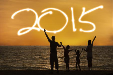 january sunrise: Silueta de la familia feliz en la playa con el n�mero 2015 en el cielo Foto de archivo