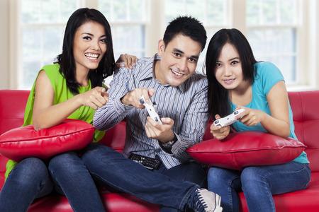 jugando videojuegos: Adolescentes felices que juegan juegos de computadora juntos