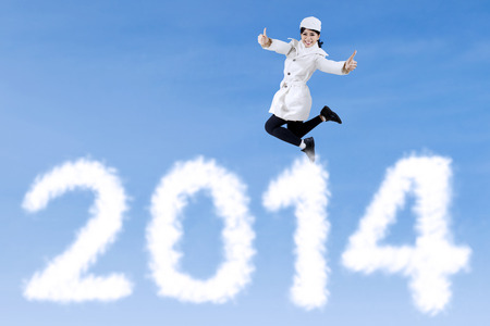 Happy winter woman is jumping over new year 2014 with ok sign photo