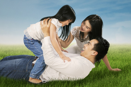 playing field: Portrait of beautiful family playing together on the meadow enjoy summer time
