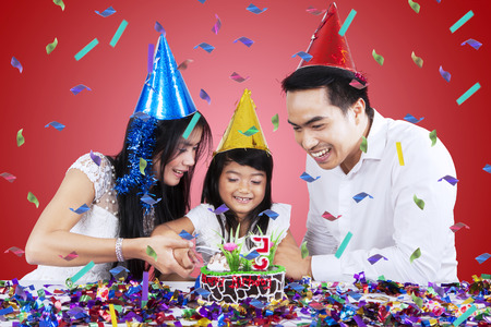 Portrait of cheerful family cutting a birthday cake together in birthday party photo