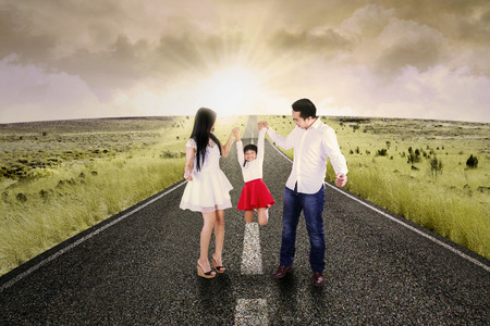 Portrait of two asian parents playing with their daughter in the morning on the road photo
