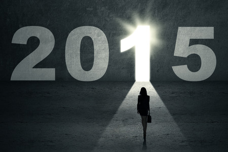 Woman carrying briefcase stepping toward bright door to future 2015 photo