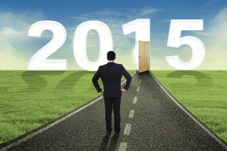 Businessman standing on the road and looking at the door to future 2015 photo