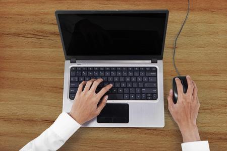 tabla de surf: Tabla Vista de ángulo alto de la persona que trabaja con el ordenador portátil en la mesa de madera