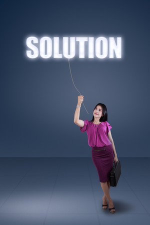Full length of female entrepreneur pulling a solution text, symbolizing she get a solution photo