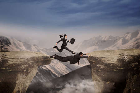 Concept of cooperation in business team. Woman runs above her partner for past the gap photo