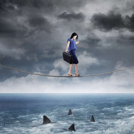 risk: Concept of business challenge with businesswoman walking on the rope above ocean