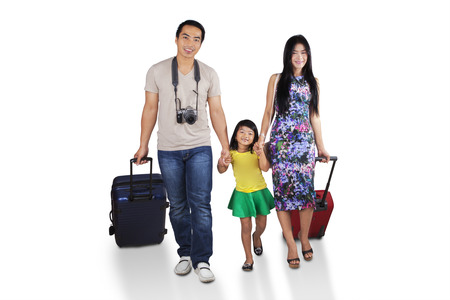 holiday destination: Portrait of asian family walking in studio while carrying luggage for holiday Stock Photo