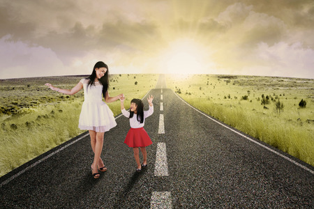 holding hands while walking: Portrait of little girl walking on the road while holding hands with her mother Stock Photo