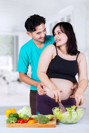 Attractive pregnant mother preparing vegetables salad with her husband at home photo