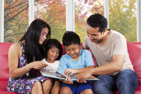 Cheerful asian children read a story book with their parents at home in autumn day photo