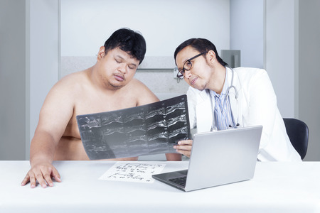 Male doctor showing and explaining the scan result of backbone to overweight patient photo