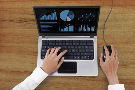 High angle view of businessman hands working with laptop computer and mouse photo