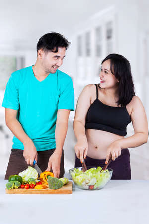 Portrait of joyful husband and his pregnant wife making salad together in kitchen photo
