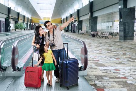 viaje familia: Retrato de familia feliz en pasillo del aeropuerto va a las vacaciones y mirando algo