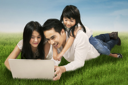Portrait of hispanic family using laptop computer while lying on grass in the meadow photo