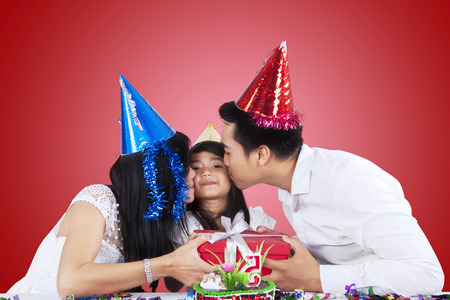Portrait of little girl receiving a gift and kiss from her parents in birthday party photo