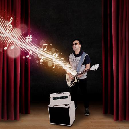 yetenekli: Yetenekli gitarist gerçekleştirmek ve bir sahnede bir olay gitar çalmak