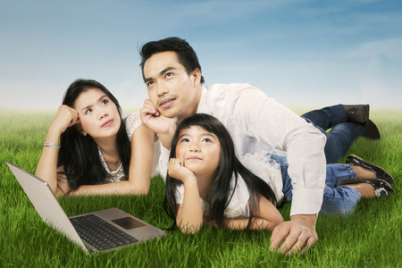 Portrait of happy asian family daydreaming together on the meadow photo