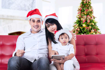 Family in santa hats using a digital tablet at home photo
