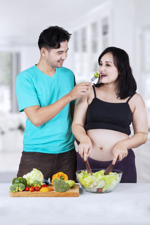 Portrait of asian husband giving healthy food to his pregnant wife in the ktichen photo